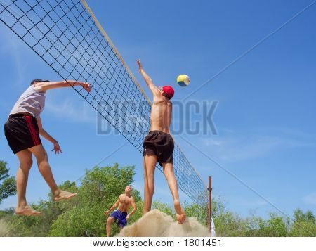 Three Men Playing Beach Volleyball - Teenager Blocks A Tall Guy Over Net