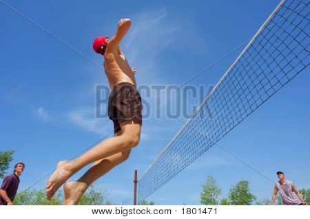 Three Teenagers Playing Beach Volleyball - Boy In Red Hat Jumps High To Spike