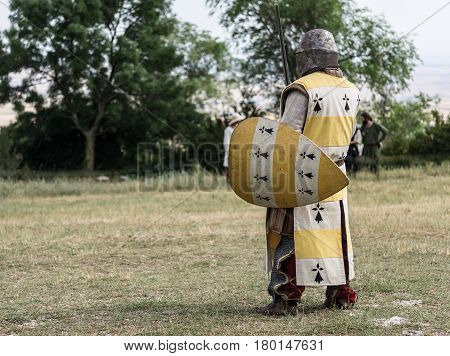Medieval knight ready for battle, reenactment with costumed characters and medieval armor with chainmail, helmet swords and shields. Medieval demonstration and recreation