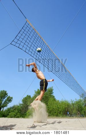 Teenager Playing Beach Volleyball - Jumps High With Beautiful Splash Of Sand