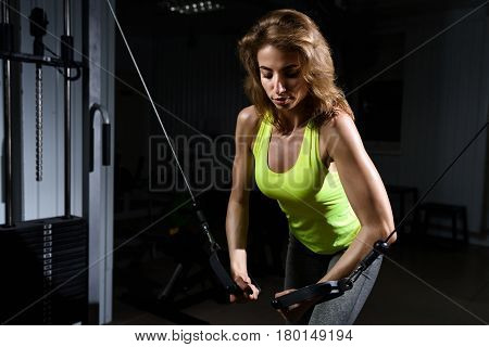 Girl in the gym doing exercises in the squat rack looking down.