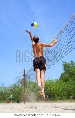 Playing Beach Volleyball - Short Balding Man Hits The Ball