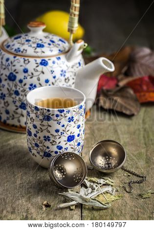 Autumn cup of tea with a teapot on rustic table with tea strainer and salvia in front.
