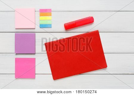 Flat lay of bright office stationery supplies - colorful markers, sticky notes and memo blocks, notepad on white rustic wood background, top view with copy space, nobody, objects