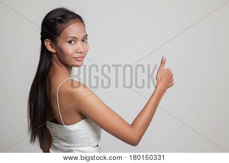 Young Asian Woman Turn Back Thumbs Up.