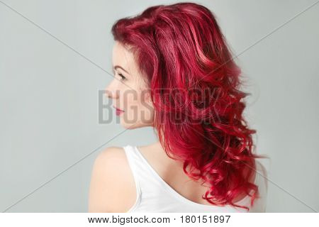 Beautiful young woman with dyed curly hair indoors