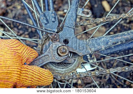 Hand with a wrench and a nut on a bicycle wheel