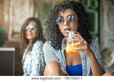 Pretty girls sit on the multicolored wall background. They wear the light shirts with patterns and sunglasses. Curly woman drinks a cocktail from glass jar. Closeup low aperture photo. Horizontal
