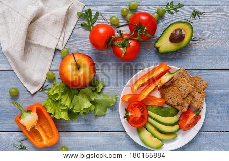 Healthy eating. Fresh vegetables and fruits, sliced and scattered on bright blue wood background. Vegetarian food with copy space.