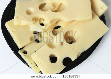 Sliced cheese laid out on a black ceramic saucer