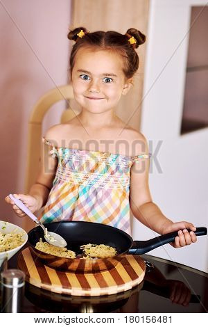 Cute little girl cooking potato pancakes at home