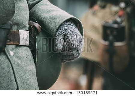Close up of German military ammunition of a German soldier at World War II. Warm autumn clothes, soldier's overcoat, gloves, helmet