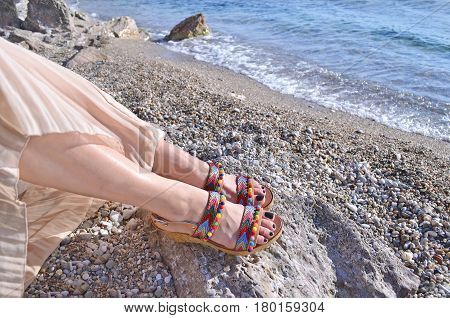 greek model advertises bohemian sandals on the beach