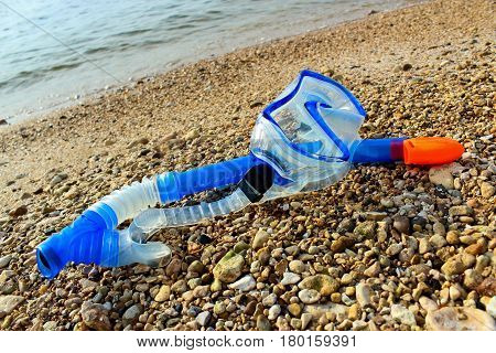 Scuba mask and snorkel on the rocky shore of the pond