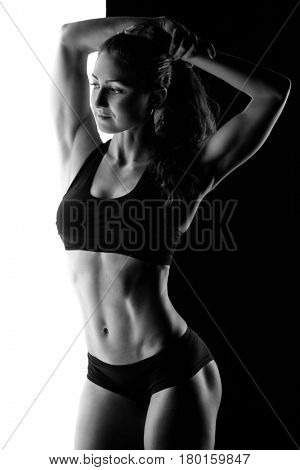 Silhouette of sporty female in studio in black and white