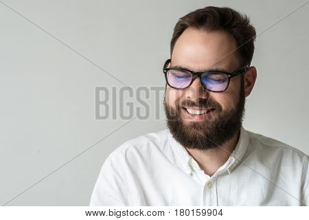 Closeup studio portrait of positive man with beard and glasses isolated