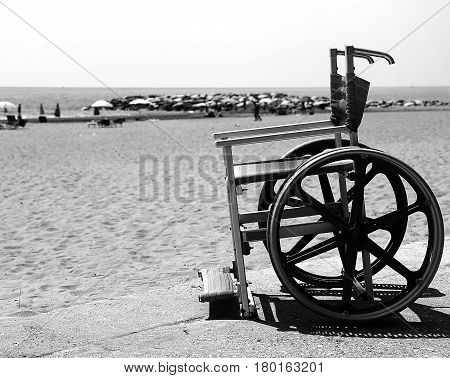 Wheelchair With Stainless Wheel On The Beach With Black And Whit