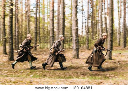 Pribor, Belarus - April 23, 2016: Three Re-enactors Dressed As Soviet Russian Red Army Infantry Soldiers Of World War II Running With Rifles In Forest At Spring Season.