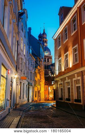 Riga, Latvia. View Of Deserted Narrow Cobbled Kramu Street Of Old Town In Bright Evening Illumination With Ancient Architecture Leading To Dome Cathedral Under Summer Blue Sky.