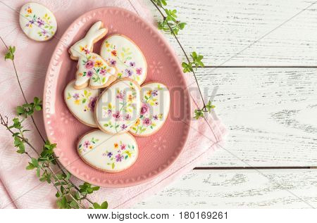 Biscuits colorful Easter cookies on white wooden background. Floral icing decorated cookies.