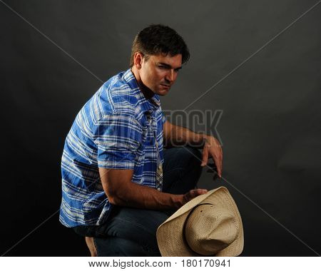 The handsome cowboy is crouched down with his hat.