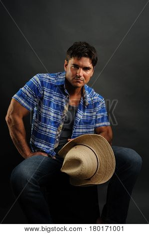 The muscular cowboy shows off his biceps