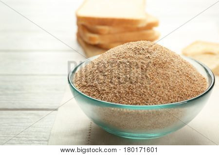 Small bowl of bread crumbs on wooden background
