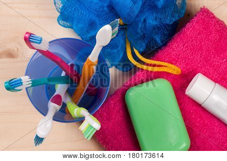 Toothbrushes, soap, sponge, towel on a wooden table. hygiene products. Body care Top view