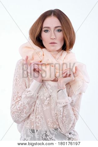 Female portrait in half-growth on white background. Red-haired woman in big beige scarf and lace blouse. She looks in the camera, red healthy hair. Isolated shot
