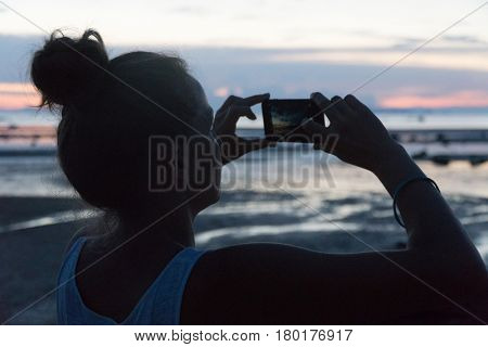 Woman takes a sunset above the sea on a phone camera.