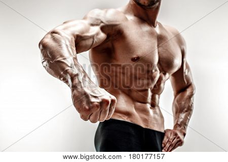 Handsome muscular bodybuilder demonstrates his fist and vein, blood vessels. Studio shot on white background. Mans hand