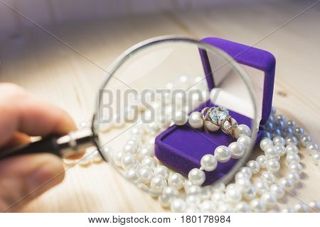 A bright gold ring with a large gem in a velvet lilac gift box surrounded by pearl beads under a magnifying glass