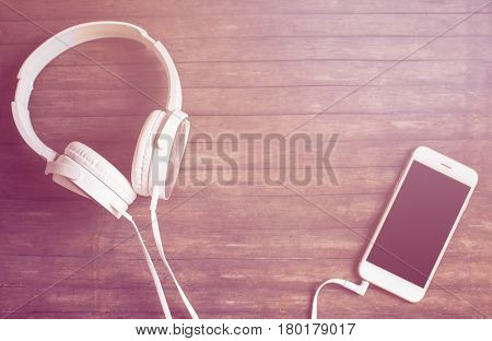 White phone and headphones flat lay on wooden table. Warm pink light toned photo. Smartphone and earphones vintage banner template with text place. Music listening concept image. Black screen phone