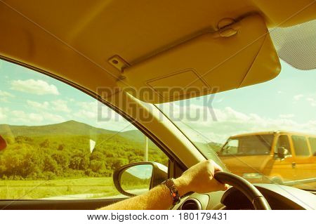Man's Hand On Steering Wheel, Car Rides Along Road Against Background Of Green Grass And Mountains,