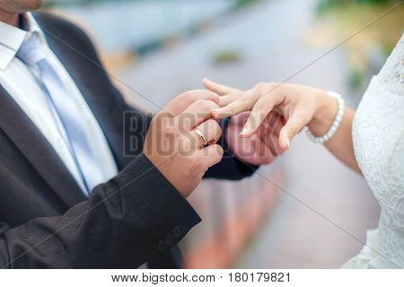 Groom wears bride a wedding ring on his finger. A couple betrothed in the street. Wedding ceremony - hands closeup.