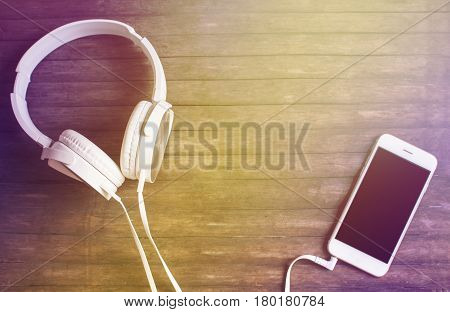 White phone and headphones on wooden table. Warm yellow light toned photo. Smartphone and earphones vintage banner template with place for text. Music listening concept image. White hipster device