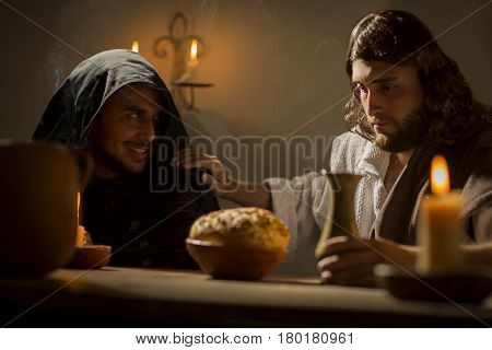 Judas looking at Jesus Christ with maiicous look during the last supper