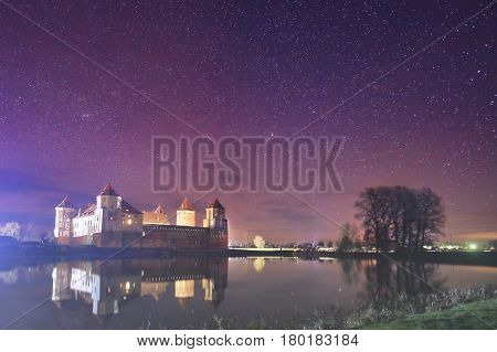 Night landscape of the old castle in the background of the starry sky and the lake. Colorful starry night sky. The flickering lights of the stars. A beautiful milky way. Stone palace on the lake shore at night. The Mir Castle.