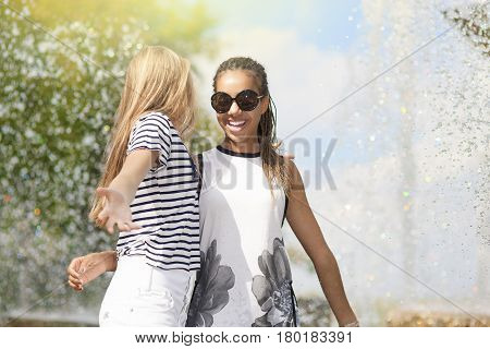 Teenagers Concepts and Ideas. Two Teenage Girfriends Embracing Together. Posing Against Fountain in Park Outdoors. African American Model and Caucasian Blond Model.Horizontal Shot