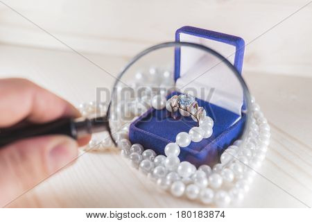 A bright gold ring with a large topaz in a blue velvet gift box surrounded by pearly beads under a magnifying glass. Gift to your beloved woman concept