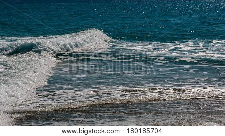 The Surf Of The Blue Turquoise Sea With White Perpendicular Waves On The Sandy Beach