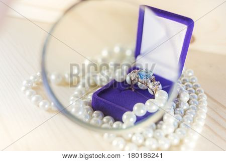 A bright gold ring with a large blue topaz in a velvet lilac gift box surrounded by beads of pearls under a magnifying glass on a light wooden background.Gift to your beloved woman concept