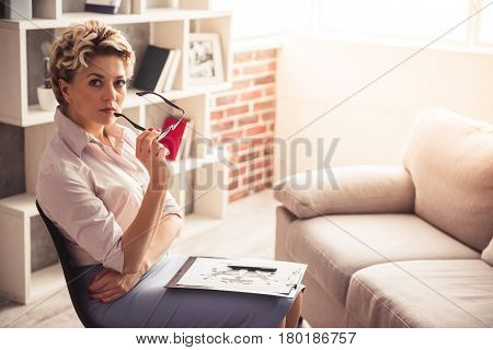 Beautiful psychotherapist is holding eyeglasses and looking at camera while sitting in her office