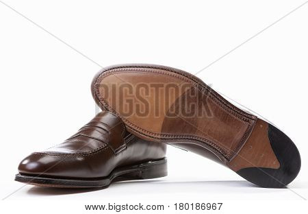Footwear Concepts. Pair of Stylish Brown Penny Loafer Shoes Against White Background with One Item Reversed. Horizontal Image Composition