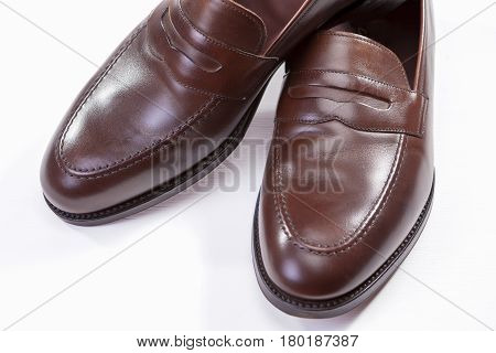 Footwear Concepts. Closeup of Pair of Stylish Brown Penny Loafer Shoes Against White Background. Horizontal Image Orientation