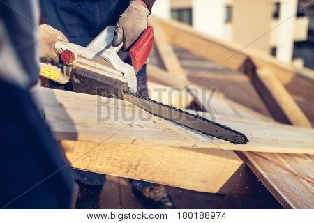 Industrial Construction Workers Cutting Timber Wood With Chainsaw. Men Sawing Using Electrical Chain
