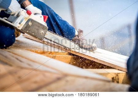Industrial Worker Cutting Timber Planks Using Electrical Saw. Details Of Construction Site