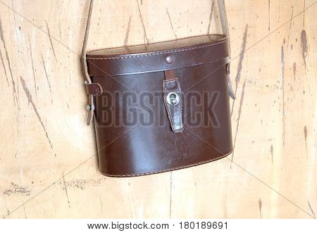 Vintage closed brown hard leather carry case for military binoculars hangs on the wall front view indoor closeup