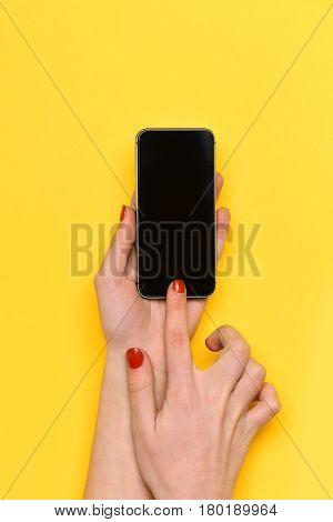 internet surfing video conferencing girl touch mobile or cell phone screen with hand has red manicure on yellow background. skincare communication copy space