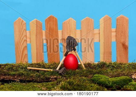 Painted Easter Red Egg At Wooden Fence On Green Moss